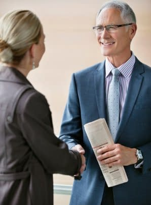 Two people shaking hands before a meeting