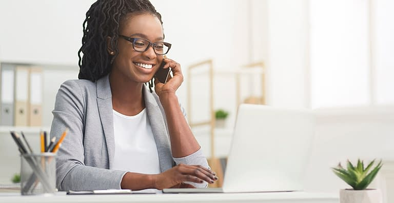 happy woman in office on phone